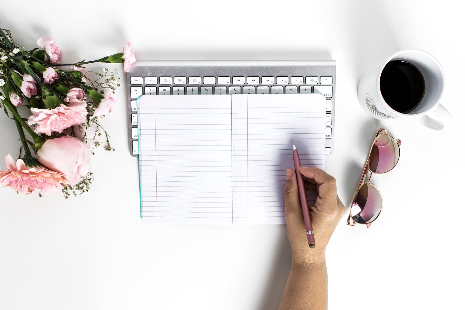 hand holding pen near notebook on desk